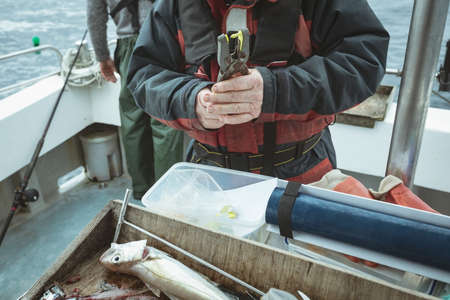 Mid section of fisherman pressing tag with hand tool LANG_EVOIMAGES