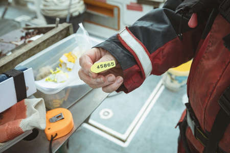 Mid section of fisherman holding number tag