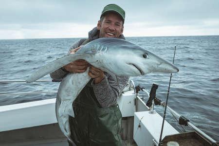 Portrait of happy fisherman holding shark fish