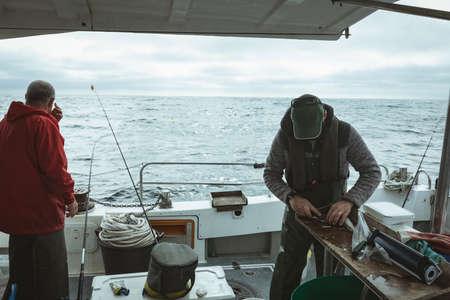 Fisherman cutting fish fillet in boat