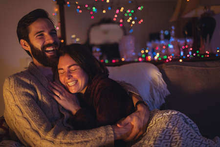Couple having fun while relaxing on sofa in living room
