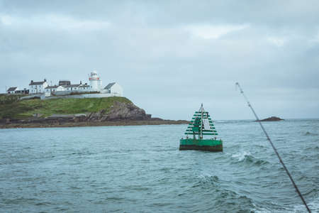 Buoy floating on sea wave with lighthouse in background LANG_EVOIMAGES
