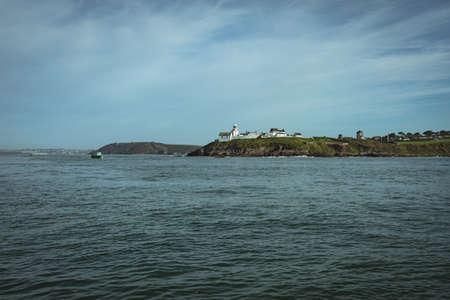 Lighthouse on cliff near sea coast