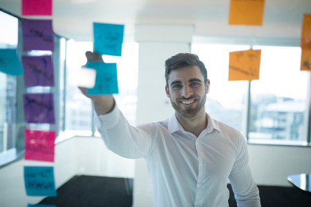 Male executive reading sticky note in office Stock Photo
