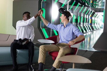 Male executives giving high five to each other in office Stock Photo