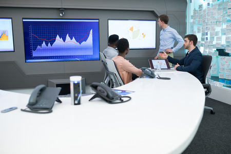 Male and female executives discussing over graph in boardroom