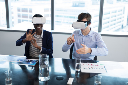 Smiling executives using virtual reality headset in office Stock Photo