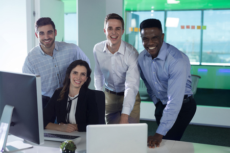 Portrait of smiling executives standing at desk in office