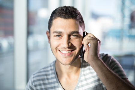Portrait of male executive talking on mobile phone in office