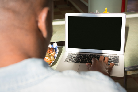 Close-up of man using laptop in the restaurant Stock Photo