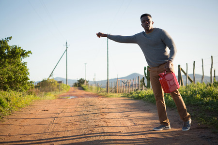 Man with petrol can hitchhiking at countryside  on a sunny day Stock Photo