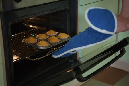 Woman putting muffins in oven at home