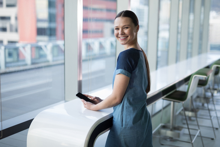 Portrait of happy female executive using mobile phone in office Stock Photo