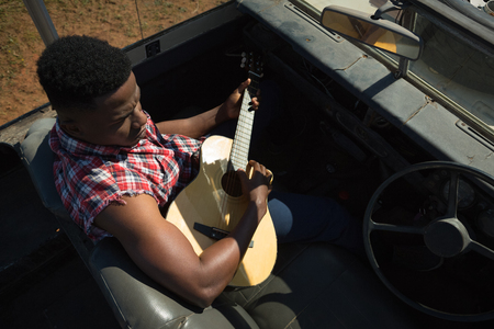 Man playing guitar in car on a sunny day Stock Photo