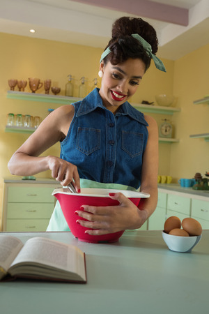 Smiling woman reading recipe while whisking mixture in the kitchen at home
