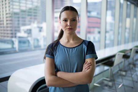 Female executive standing with arms crossed in office