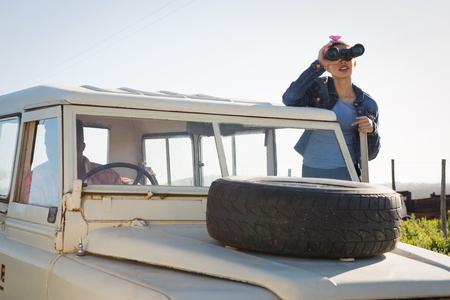 Frau , die durch Ferngläser auf einer Landschaft an einem sonnigen Tag schaut Standard-Bild - 93365723
