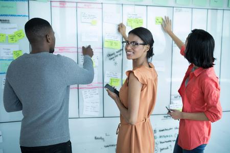 Führungskräfte vorbereiten Haftnotizen auf Whiteboard im Büro Standard-Bild - 93365730