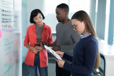 Female executive looking at graph with colleagues in background at office Stock Photo
