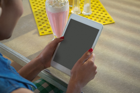 Close-up of woman using tablet while having milkshake in the restaurant Stock Photo