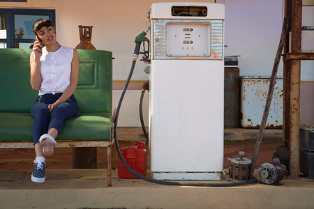 Young woman talking on mobile phone at petrol pump station