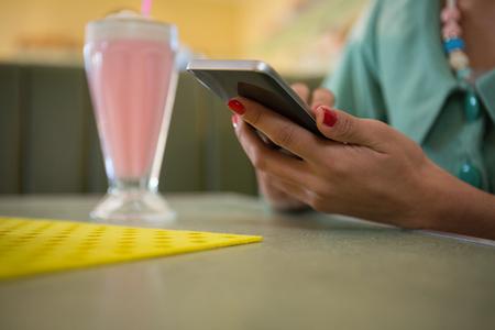Nahaufnahme der Frau sitzend im Restaurant unter Verwendung ihres Handys Standard-Bild - 93365762