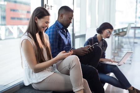 Männliche und weibliche Führungskräfte , die elektronische Geräte im Büro verwenden Standard-Bild - 93365765