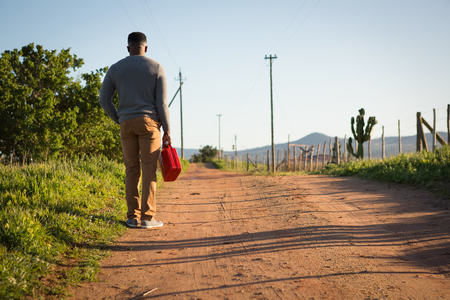Rear view of man standing with petrol can at countryside