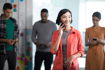 Female executive talking on mobile phone while colleagues standing in background