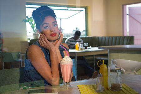 Thoughtful woman looking away while having milkshake in the restaurant