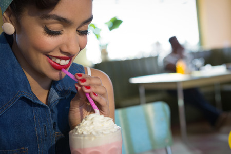 Close-up of happy young woman having milkshake in the restaurant Stock Photo