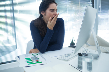 Tired female executive yawning at desk in office