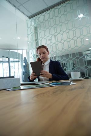 Weibliche Führungskraft mit digitalen Tablet am Schreibtisch im Büro Standard-Bild - 93513077