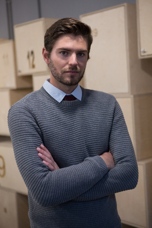 Portrait of executive standing with arms crossed in locker room at office