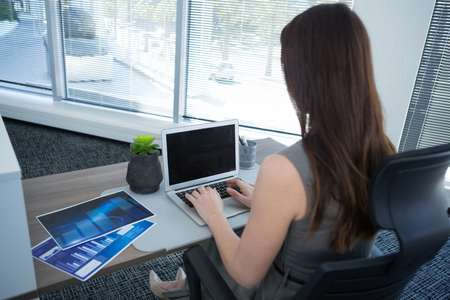 Rear view of female executive using laptop at desk in office