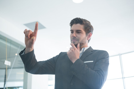 Thoughtful businessman touching invisible digital screen in office Stock Photo