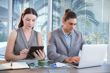 Business executives using laptop and digital tablet at desk in office
