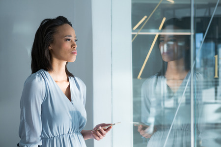 Thoughtful female executives standing with mobile phone near window Stock Photo