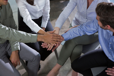 Group of executives stacking hands over each other in the office