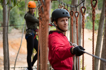 Smiling young man wearing safety helmet crossing zip line cable in background woman waiting for him in the forest