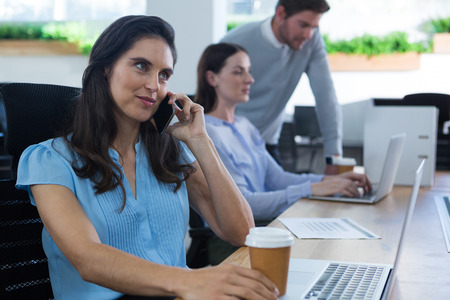 Female executive talking on phone while holding coffee mug in the office