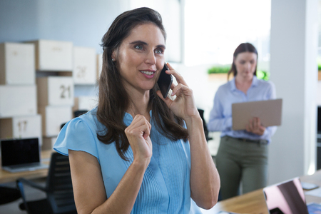 Smiling female executive talking on phone in the office Stock Photo