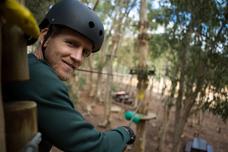Close-up portrait of smiling man wearing safety helmet looking into camera in the forest