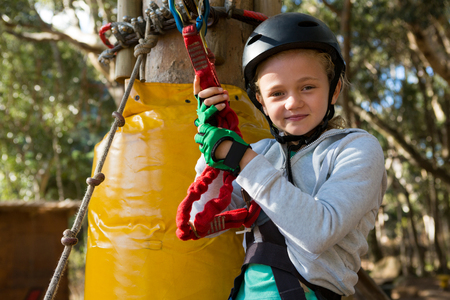 Little girl wearing helmet getting ready to ride zip line in the forest