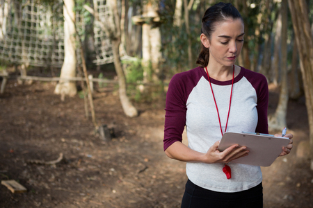 Woman standing in forest holding writing pad on a sunny day Stock Photo