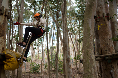 Woman wearing safety helmet swinging on rope trying to hold other rope in the forest