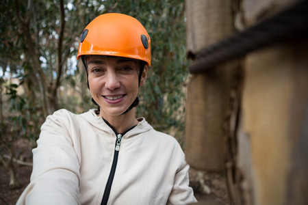 Close-up portrait of woman wearing safety helmet standing in forest Stock Photo