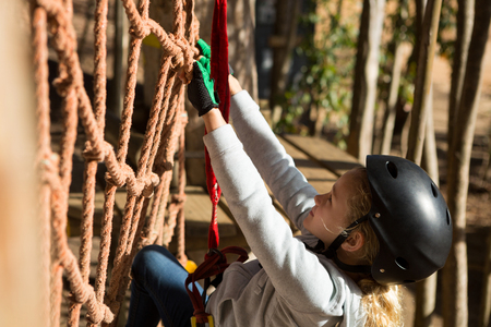 Close-up of little girl wearing helmet climbing on rope fence in the forest Stock Photo