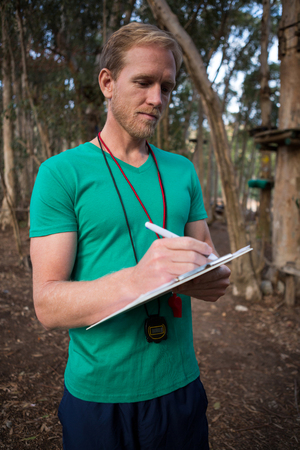 Athletic man taking notes standing in forest during daytime Stock Photo