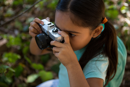 Close-up of little girl with backpack taking photo with camera on a sunny day in the forest